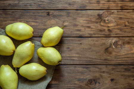Yellow pears lie on a wooden background.