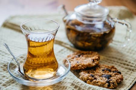 Herbal tea in a glass cup with cereal cookies and a teapot stand on a wooden table. 写真素材