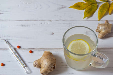 Ginger tea with a slice of lemon, yellow leaves with a thermometer, pills are on a white table. There is a copy space.
