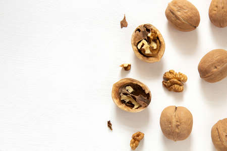 Whole and chopped walnuts on a white background. Horizontal orientation, top view, with copy space.