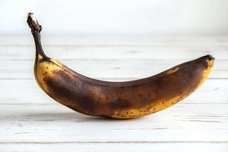 Ugly food. Dark banana spoiled over time on a white background. Horizontal orientation, side view.