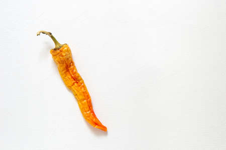 Ugly food. Wrinkled old peppers on a white background. Horizontal orientation, top view. Stok Fotoğraf