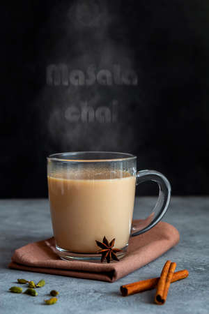 Indian tea masala chai with spices in a glass mug on a dark background. Vertical orientation, copy space