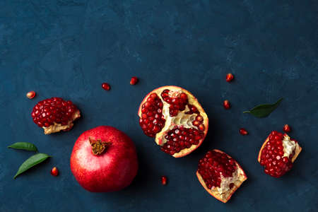 Flat lay with fresh pomegranate on a dark blue background. Top view, copy space