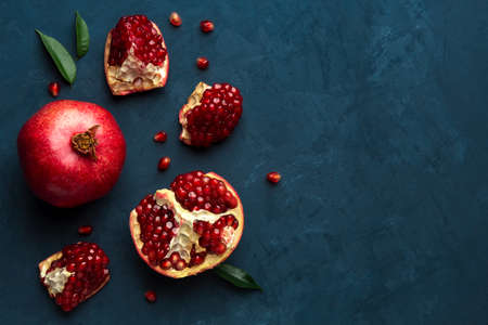 Juicy pomegranate on a blue background with place for text. View from above.