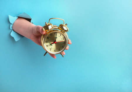Alarm clock in a female hand on a blue background with a hole, time concept. Horizontal orientation, copy space
