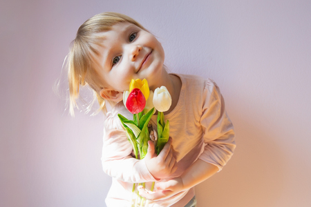 Sweet happy little blond-haired girl holding a bouquet of colorf Stock Photo