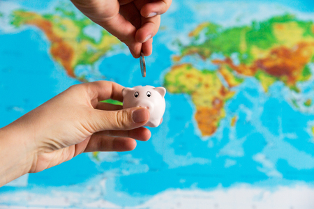 A tiny piggy bank is held in the hand. A colorful map of the wor Stock Photo