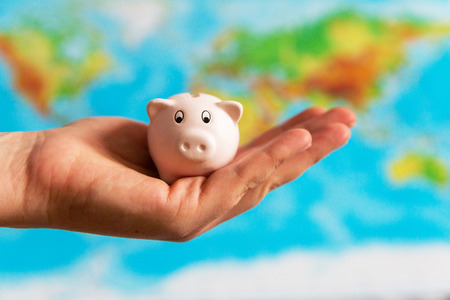 A tiny piggy bank is held in the hand. A colorful map of the world in the background. Travel concept. Collecting money for the holidays Stock Photo