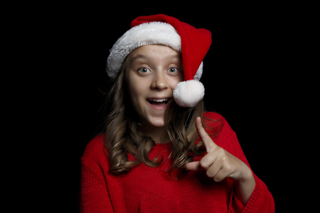 Merry Christmas. A young girl in a red sweater and a Santa Claus hat looks at the viewer and has an idea. Black isolate. Copy space. Фото со стока