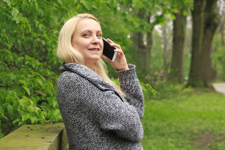 Beautiful smiling blond woman 45 years old in city park talks on a phone.