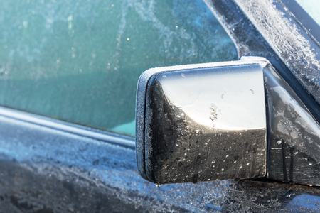 Black car passenger side of the frozen mirror. First frost.