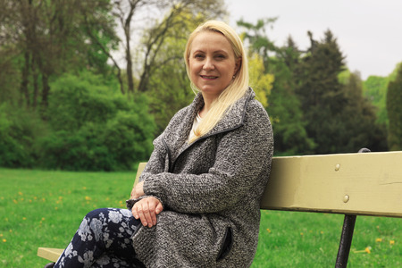 Beautiful blond woman 45 years old in city park.