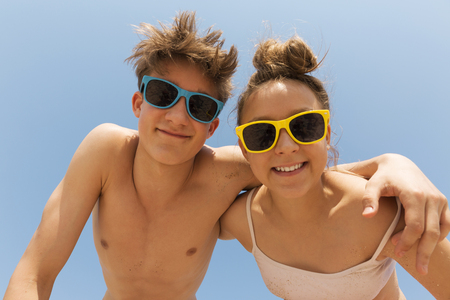 Two young and beautiful teenagers in colorful sunglasses hug on the beach against the blue sky.They are leaning towards the camera, looking at the viewer and laughing.