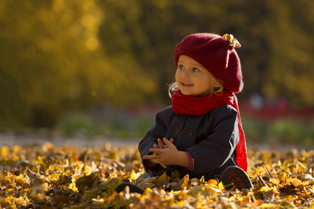 Little girl with blond hair sitting in autumn park smiles and looks at the right side. She is wearing a red beret, a scarf and a red rain boots. Close up and copy space.