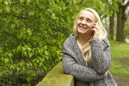 Beautiful smiling blond woman 50 years old in city park talks on a phone. Stock Photo