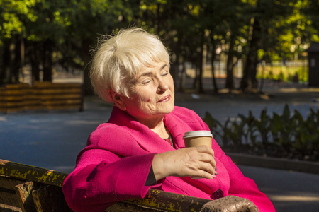 A beautiful smiling pensioner sitting on a bench in an urban park. She holds a coffee in her hand. Sunny day. Close - up.