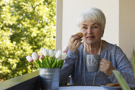 A beautiful blonde pensioner woman sitting and smiling on the terrace with a cup of tea and cookies. Copy space.