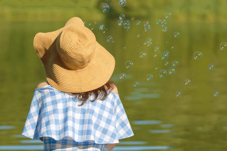 Young woman in a dress and a straw hat blowing bubbles against the background of the river. Back view. Stok Fotoğraf
