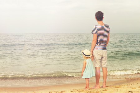 Father and daughter stand on the beach and look at the sea. Back view, copy space.