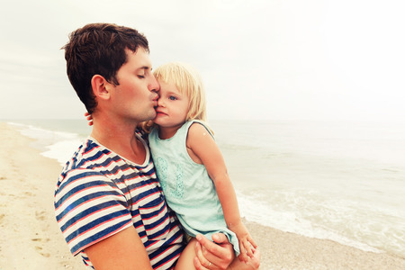 Father holds daughter on his hands and kisses her on the forehead. Family vacation by the sea. Copy space. 写真素材