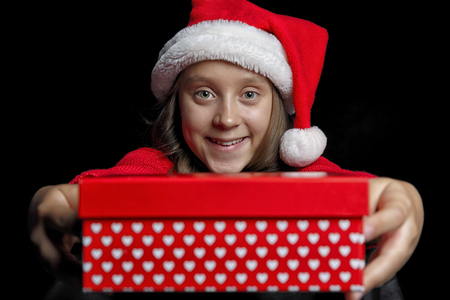 Merry Christmas. A young girl in a red sweater and a Santa Claus hat holds a present - a box and looks at the viewer. Black isolate. Copy space.