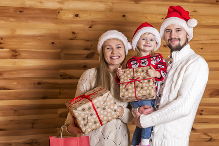 Happy family. Mom, dad and tiny daughter in Santa Clauss hat with presents on a wooden background.