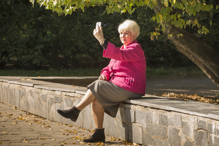 Senior beautiful blond woman makes selfie on a phone in sunny day.
