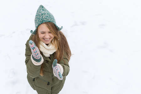 A young beautiful girl with long blond hair enjoys the first snow. Green jacket, green hat and gloves. Top view. Copy space. Imagens