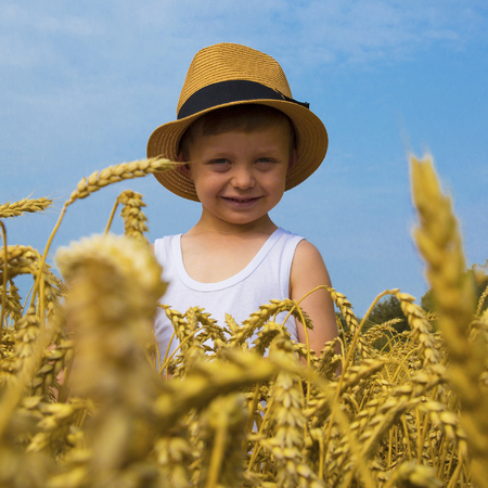 Happy family. Little charming happy boy in a hat laughs in the wheat field. Front view. Stock Photo