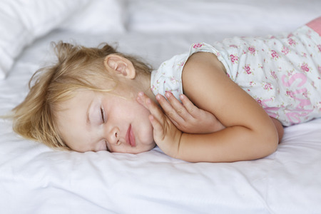 Sweet little blond girl sleeps in bed with her parents. White background.