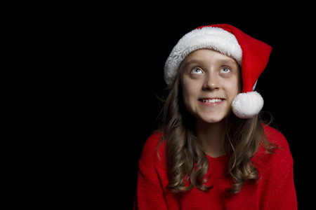 Merry Christmas. A young girl in a red sweater and a Santa Claus hat looks at the viewer. Black isolate. Copy space.