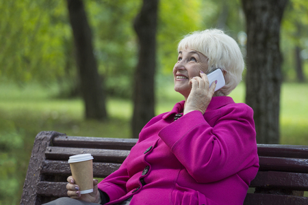 A nice retired pensioner drinks takeaway coffee and talks on the phone on a bench in a city park.