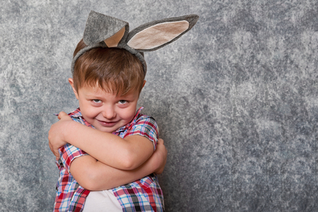 A funny, grumpy little boy dressed in a red checkered shirt and an old-fashioned hat, has a rabbit's ears on his head. Copy space. Фото со стока