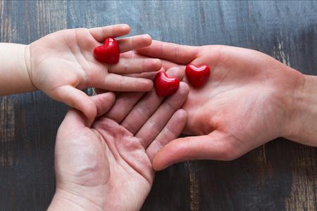 Trzy pary rak: mamy, tata i dziecka na drewnianym rustic tle. W rekach trzymaja trzy czerwone serca. Top view, copy space.