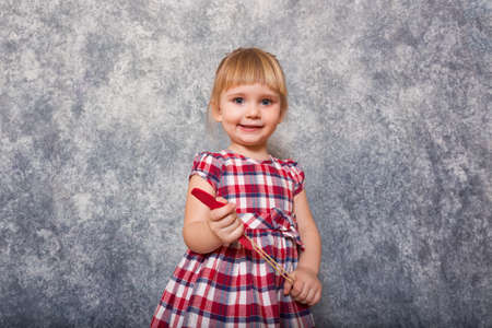 A tiny sweet girl with blond hair wearing a red checkered dress. She makes faces on a gray background. Wide angle and copy space. Child day.
