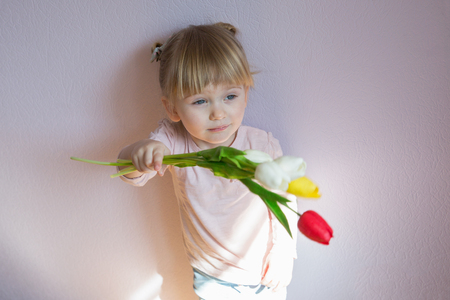 Mother's day. A serious little girl with blond hair is holding a bouquet of colorful tulips in the hands. Shot 3/4. Copy space. 写真素材