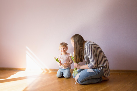 Happy family. Daughter gives a bouquet of flowers (tulips) to her mother in the room. Naturally laughed. Mothers Day. Stock Photo