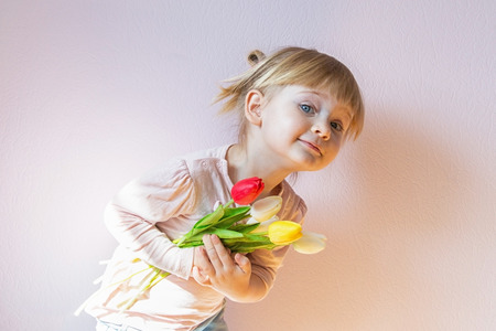 Sweet happy little blond-haired girl holding a bouquet of colorful tulips in her hands. Shot 34. Copy space.