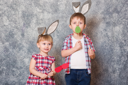 Two children, a girl and boy with Easter rabbit ears on head laugh and play. They hold colorful Easter eggs made of cardboard in their hands. Copy space.