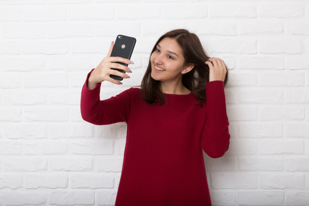 A young pretty smiling girl is holding a mobile phone in the hand against a white brick loft-style wall. Copy space.