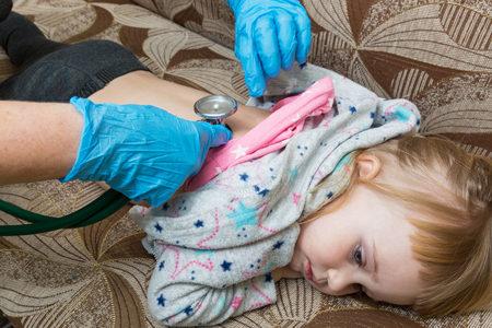 A pediatrician doctor examines the back of a sick girl using a phonostage. Home visit.