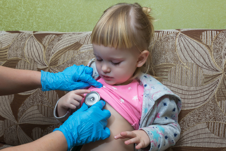 The pediatrician examines the sick girls breasts using a phonostage. Home visit. Stock Photo