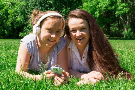 Two beautiful girls: younger and older, learn foreign languages on the grass in the city park. Spending time with a friend in the park.
