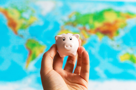 A tiny piggy bank is held in the hand. A colorful map of the world in the background.