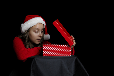 Merry Christmas. A young girl in a red sweater and a Santa Claus hat holds a present -  box and a hole in the middle. Black isolate. Copy space. Stock Photo