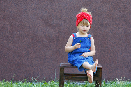 Little girl with polka-dot headband laughs and looks at the viewer. Copy space.