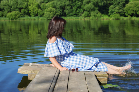Young woman resting on a wooden bridge and wets feet in the river. Sunny sumer day.
