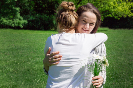 A girl with blond hair combed in a bun, gives her mother a bouquet of white flowers for Mother's day. 26th of May. 免版税图像