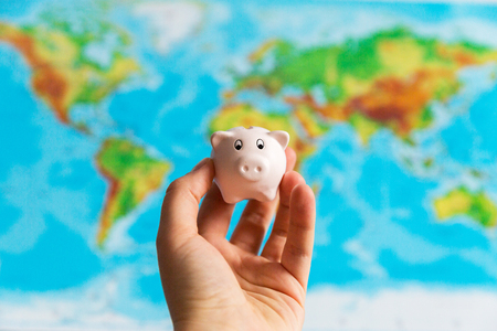 A tiny piggy bank is held in the hand. A colorful map of the world in the background. Travel concept. Collecting money for the holidays 免版税图像